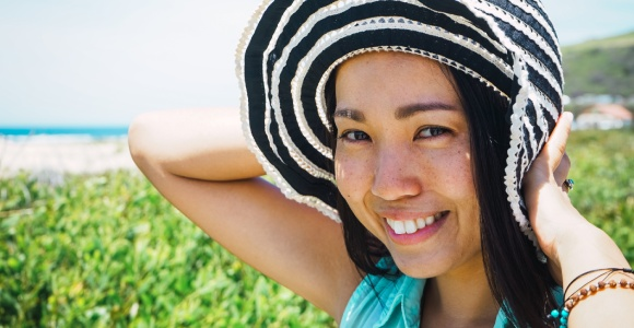 Asian woman under the sun with a hat but no sun glasses