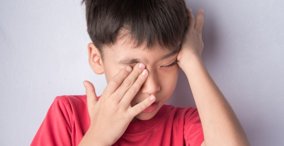 Young kid rubbing his eyes
